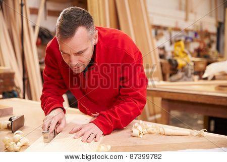 Carpenter Planing Wood In Workshop