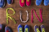 picture of signs  - Six pairs of running shoes and shoelaces run sign on a wooden floor background - JPG