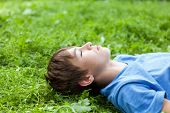 picture of schoolboys  - Happy teenager lying on grass in park outdoor schoolboy - JPG
