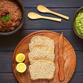 picture of kidney beans  - Overhead shot of wholegrain bread slices on wooden plate with two rustic bowls of homemade vegetable spreads  - JPG