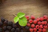 image of blackberries  - raspberries and blackberry scattered on the wooden table - JPG