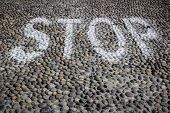 image of paved road  - Detail of a paved road with stop sign - JPG