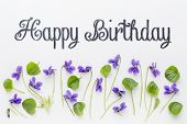 stock photo of viola  - Happy birthday greetings with fresh viola flowers  and leaves on white art canvas - JPG
