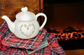 stock photo of cozy hearth  - A teapot and a book by the fireplace in a cold winter night - JPG