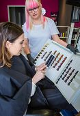 stock photo of hair dye  - Beautiful young woman with hairdresser taking a photo with her smartphone to the hair dye palette - JPG