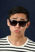 stock photo of disappointed  - Disappointed young Asian man in sunglasses - JPG