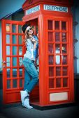 stock photo of phone-booth  - Pretty young woman talking on the phone in telephone booth - JPG
