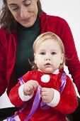 picture of santa baby  - one year age caucasian blonde baby Santa Claus disguise with brunette woman mother red cardigan green trousers opening silver wrapped paper box gift Christmas on white background - JPG