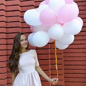 stock photo of latex woman  - happy young woman standing over red brick wall and holding pink and white balloons - JPG