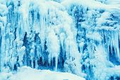 foto of frozen  - Frozen waterfall of blue icicles on the rock - JPG