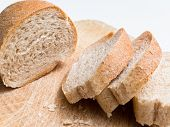 picture of bread rolls  - Slices of a wholegrain bread roll on a wooden cutting board - JPG