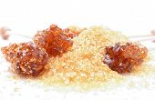 picture of white sugar  - Brown sugar crystal on wooden stick and brown granulated sugar on a white background - JPG