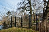 stock photo of wrought iron  - Green painted wrought iron fence with a locked gate in front of an historic country house in the Netherlands - JPG
