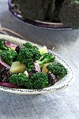 image of olive shaped  - Broccoli and potatoes salad with olives and red onion on a beautiful plate elongated shape - JPG
