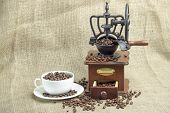 foto of coffee coffee plant  - white tablecloth on the table or burlap old coffee grinder filled with coffee beans next to a white porcelain cup filled with coffee beans two croissants - JPG