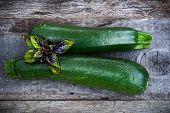 foto of basil leaves  - Fresh green zuchinni with basil leaves on wooden board top view - JPG