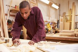 stock photo of joinery  - Apprentice Planing Wood In Carpentry Workshop - JPG