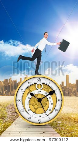 Happy businessman leaping with his briefcase against path on grass with cityscape on horizon