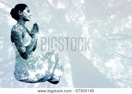 Content brunette in white sitting in lotus pose against low angle view of tall trees
