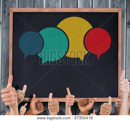 Hands showing thumbs up against blackboard with copy space on wooden board
