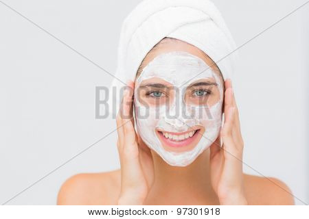 Portrait of an attractive woman having white cream on her face at spa center