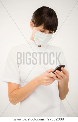 Portrait of a nurse using her mobile phone on white background