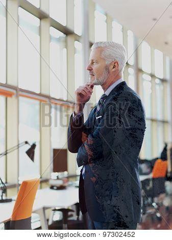 Double exposure design. Portrait of senior business man with grey beard and hair alone i modern office indoors