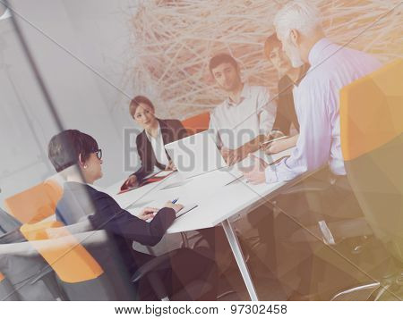 Double exposure with  low poly design. Business people group on meeting at modern bright office indoors. Senior  businessman as leader in discussion.
