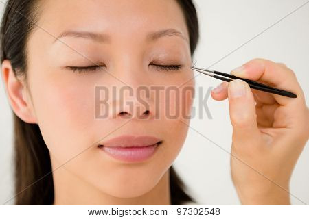 Close up view of woman placing fake eyelash on a patient at the spa health