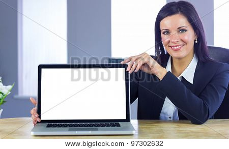 Confident businesswoman showing her laptop in her office