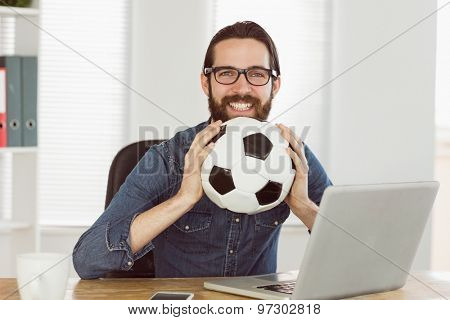 Hipster businessman holding a football in his office