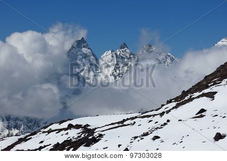 Mountain Peaks Reaching Ot Of Clouds