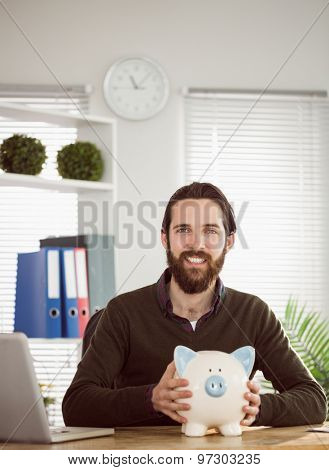Hipster businessman with a piggy bank in his office