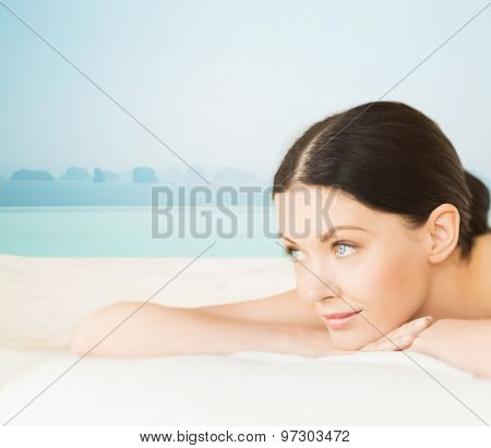 people, beauty and body care concept - happy beautiful woman lying on massage desk at spa resort over sea and infinity pool background