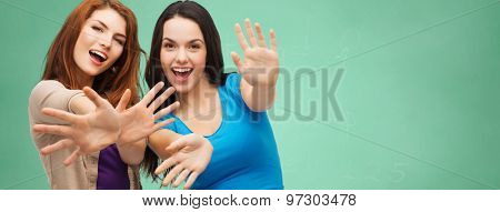 school, education, happiness and people concept - two smiling student girls or young women showing their palms over green chalk board background