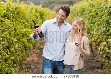 Happy couple looking at wine bottle in the grape fields