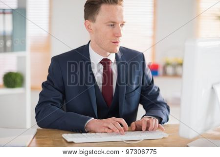 Stylish businessman working at his desk in his office