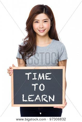 Young woman with chalkboard showing phrase of time to learn
