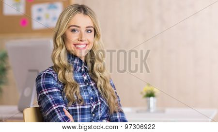 Pretty casual worker smiling at camera in her office