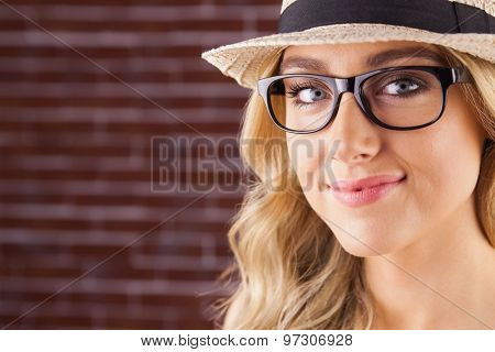 Portrait of gorgeous blonde hipster smiling against red brick background