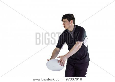 Rugby player doing a side pass on a white background