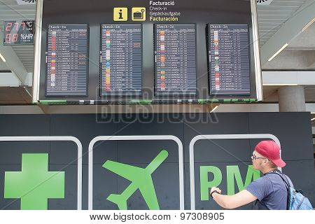 Young Man By Airport Info Board
