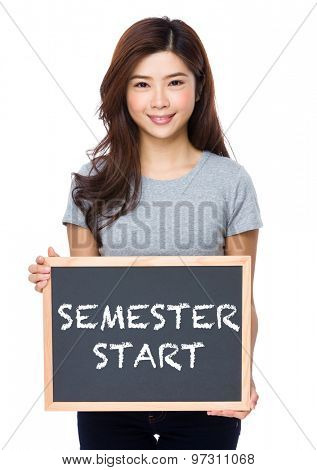 Young woman with chalkboard showing semester start