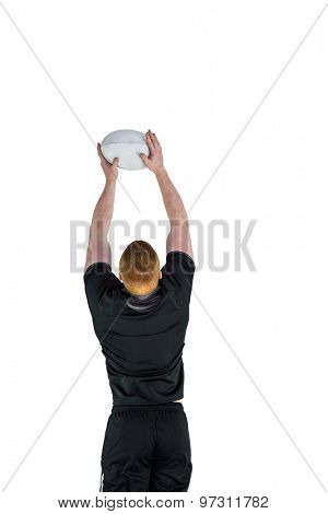 Rugby player catching a rugby ball on a white background