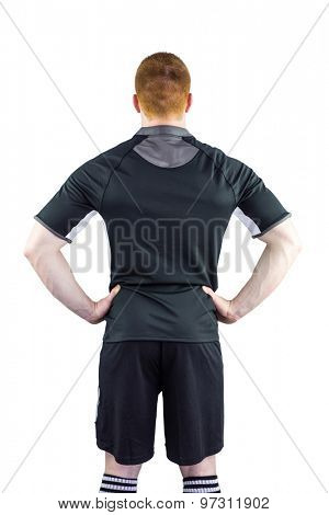 Back view of a rugby player with hands on hips