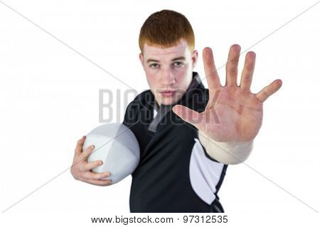Portrait of a rugby player gesturing stop sign while holding a ball