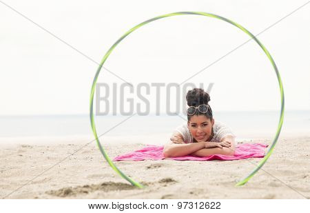 Smiling woman looking at camera through hula hoop at the beach
