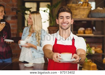 Portrait of a waiter handing a cup of coffee at the coffee shop