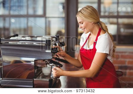 A pretty barista preparing coffee at the coffee shop
