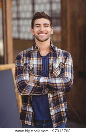 Portrait of smiling casual waiter with arms crossed at coffee shop